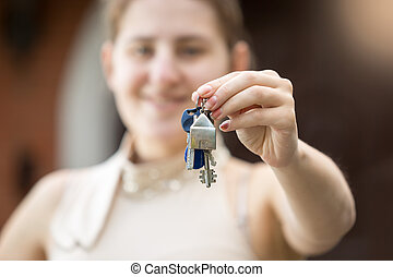 Closeup of young woman holding key from new house - Closeup...