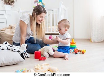 Happy mother and her baby playing with to cell phone - Happy...