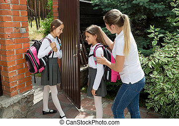 Caring mother seeing off her daughters to school - Young...