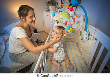 Portrait of young mother looking at her baby in crib before...