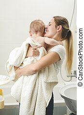 Young mother kissing her baby at bathroom after having bath...
