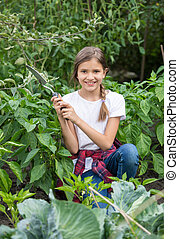 Beautiful smiling teenage girl working at garden