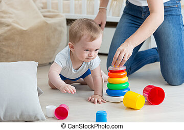 Adorable baby crawling on floor and assembling toy tower with mother