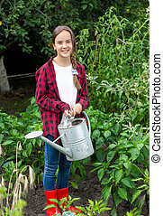Young girl in red rubber boots watering vegetables at garden