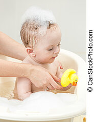 Cute baby boy playing in foam bath with yellow rubber duck -...