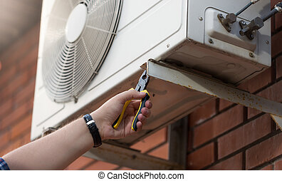 Closeup photo of technician installing outdoor air conditioning unit