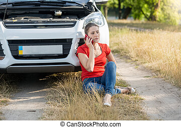 Portrait of woman sitting next to broken car and calling for...