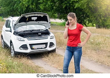 Woman standing at broken car on rural road and calling on...