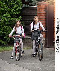 Smiling girls in uniform riding to school on bicycles -...