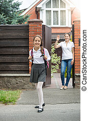 Smiling girl going out of the house backyard to school -...