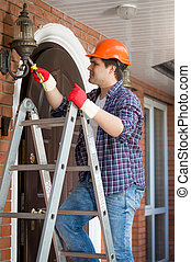 Electrician in hardhat standing stepladder and repairing lamp on house outdoor wall