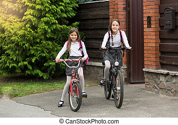 Two girls in school uniform with bags riding to school on...