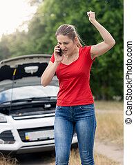 Angry woman shouting in mobile phone because of the broken...