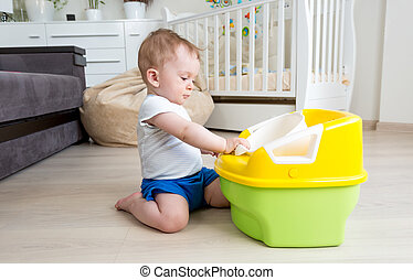 Adorable baby sitting on floor and looking at chamber pot