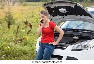 Portrait of woman leaning on broken car with open hood and...