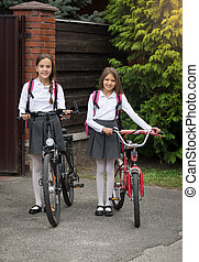 Smiling girls going to school with bicycles
