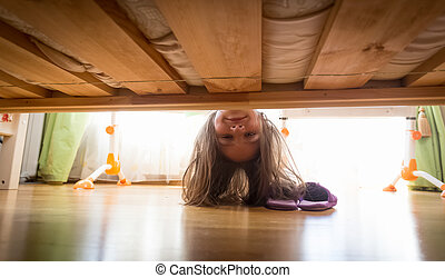 Beautiful smiling teenage girl looking under the bed for...