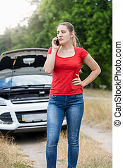 Frustrated woman calling for help with her broken car at...