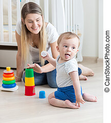 Smiling mother assembling toy pyramid with her baby boy