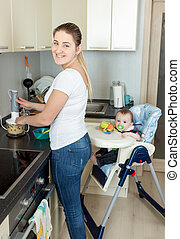Smiling woman preparing food for her 9 months old baby boy -...