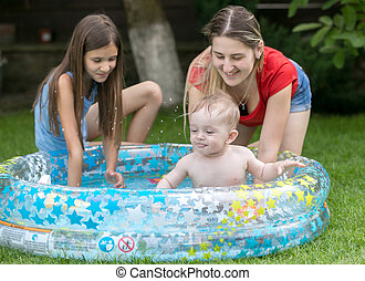 Cute baby swimming in outdoor pool with mother and elder...