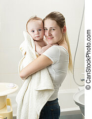 Portrait of young mother holding her baby after having bath...