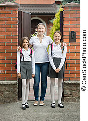 Beautiful girls standing with their mother in doorway before...