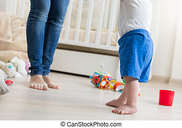 Closeup of 10 months old baby boy making first steps at...