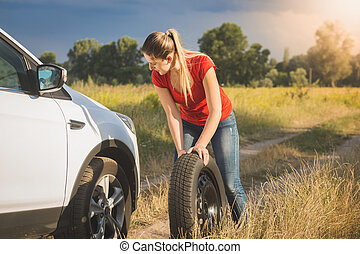 Beautiful woman rolling spare tire to change the flat one -...
