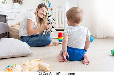Cheerful mother playing in puppet show with her baby boy