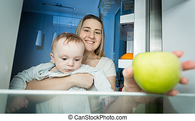 Young mother holding baby and taking green apple from apple. View from inside of refrigerator