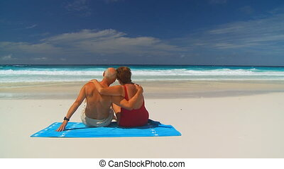 elderly couple hugging on beachtowel