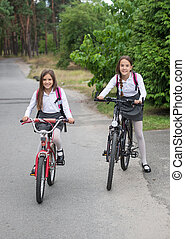Two schoolgirls riding to school on bicycles