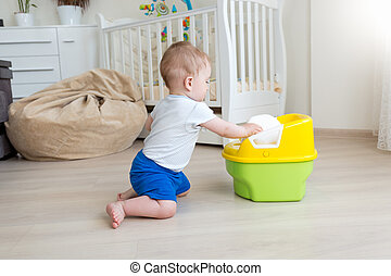 10 months old baby boy trying to sit on chamber pot at...