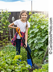 Cute 10 year old girl working at garden and digging soil at...