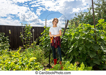 Teenage girl working with shovel at garden