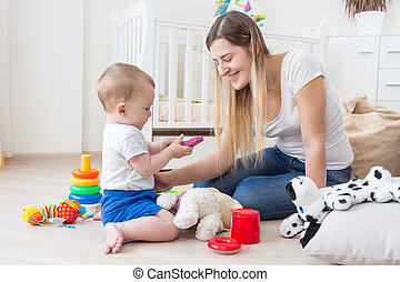 Adorable baby playing with toy cellphone on floor at living...
