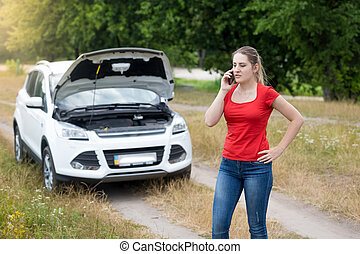Angry woman calling for help next to broken car in meadow -...