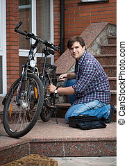 Man repairing bicycle on porch of his house - Young man...