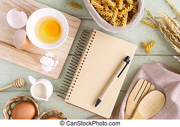 Open recipe book on green wooden table with copy space