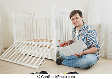 Toned photo of young man assembling furniture by himself in new apartment