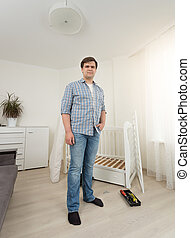 Young man in jeans posing in bedroom with disassembled...