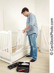 Handyman assembling white baby crib in new apartment - Young...
