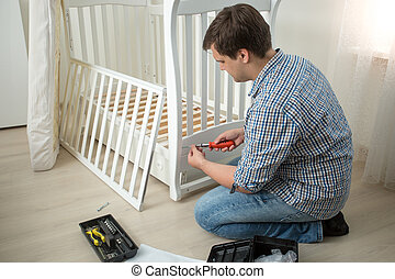 Man assembling baby's cot after moving in new house