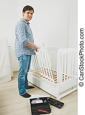 Handsome man in jeans and shirt assembling babys cot - Young...
