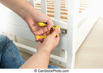 Closeup of man disassembling white wooden bed - Closeup...