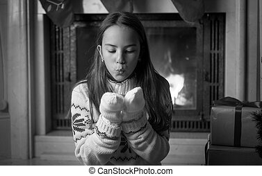 Black and white portrait of teenage girl sitting at fireplace and blowing snow from hands