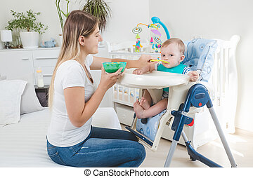 Beautiful mother feeding her baby boy in highchair with porridge