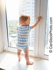 Baby boy standing on window sill and pulling window handle, Concept of children in danger