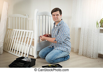 Happy man assembling white wooden crib in nursery - Happy...